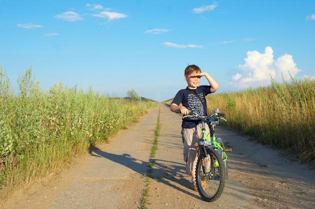 O garoto de bicicleta na estrada longa