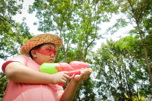 O garoto de óculos vermelhos, segurando uma pistola de água, tocando no dia songkran da tailândia