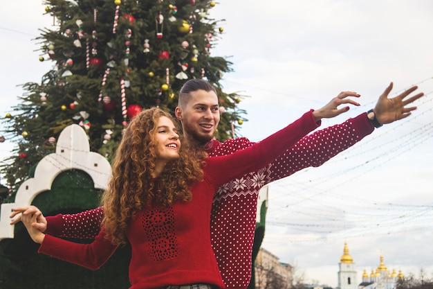 O garoto e a garota de camisola vermelha estão sorrindo alegremente para a árvore de natal.
