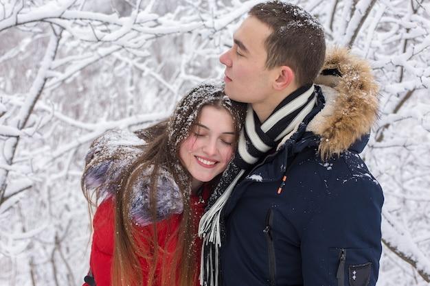 O garoto e a garota descansam na floresta de inverno. marido e mulher na neve.