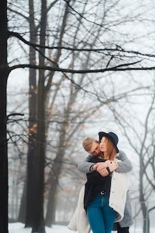 O garoto e a garota estão descansando na floresta de inverno.