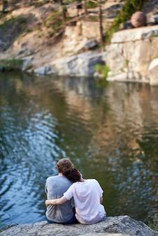 O garoto e a garota estão sentados em um penhasco acima do rio e olhando em frente. visão traseira. casal apaixonado.