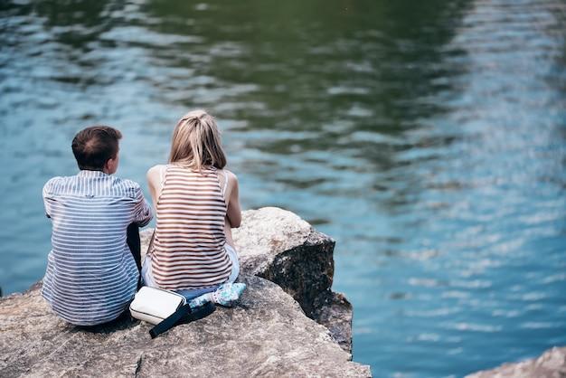 O garoto e a garota estão sentados em um penhasco acima do rio e olhando na frente