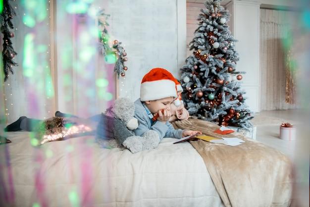 O garoto escreve para o papai noel. noite de natal em família. presentes de ano novo. sala luminosa decorada