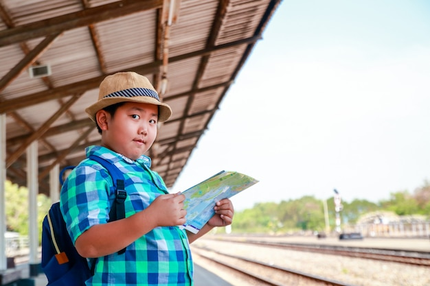 O garoto está segurando um mapa esperando o trem viajar.