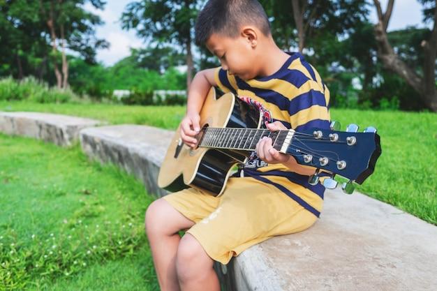 O garoto está tocando violão no jardim.