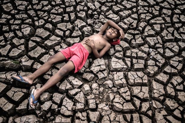 O garoto estava deitado, colocando as mãos na barriga e na testa em solo seco.