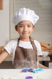 O garoto fazendo padaria caseira com felicidade