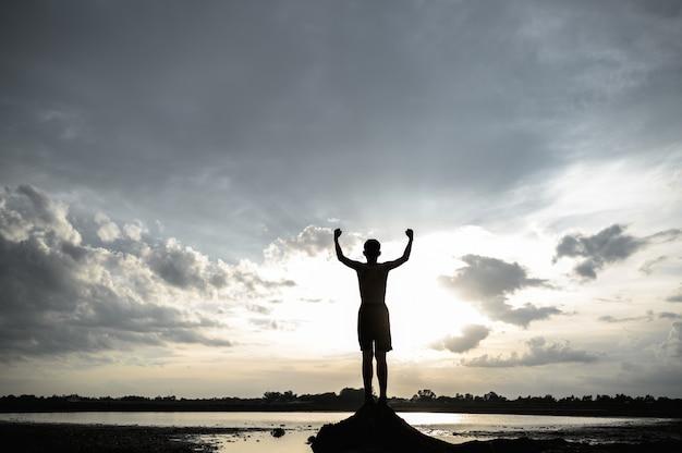 O garoto levantou a mão no céu para pedir chuva durante o pôr do sol.