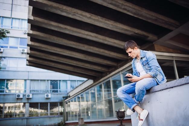 O garoto moreno com jaqueta de jeans levanta fora