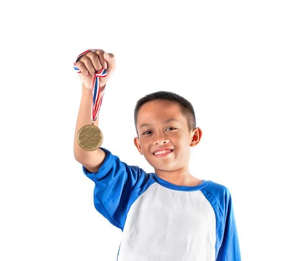 O garoto mostra a medalha de ouro, feliz e orgulhoso.