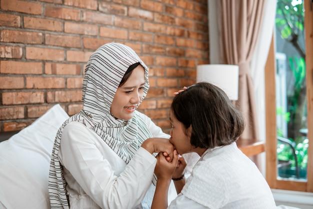 O garoto respeita a mãe apertando a mão e o beijo