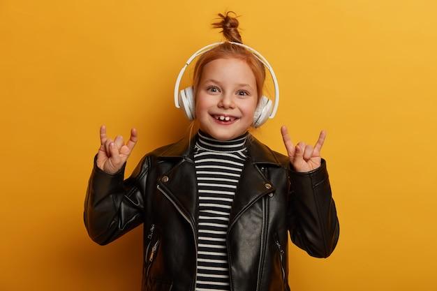 O garoto roqueiro otimista faz sinais de trompa com os dedos, gosta de ouvir heavy metal em fones de ouvido, tem um nó de cabelo sexy, usa jaqueta de couro, sente-se animado e radiante, relaxa dentro de casa