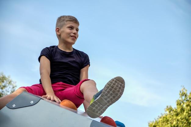 O garoto senta-se no parque em uma colina e parece longe contra o céu azul. copie o espaço.