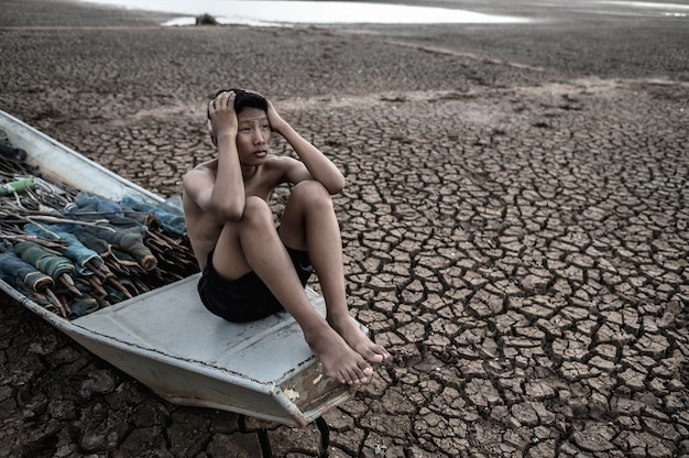 O garoto sentou-se em um barco de pesca e pegou a cabeça em solo seco, aquecimento global