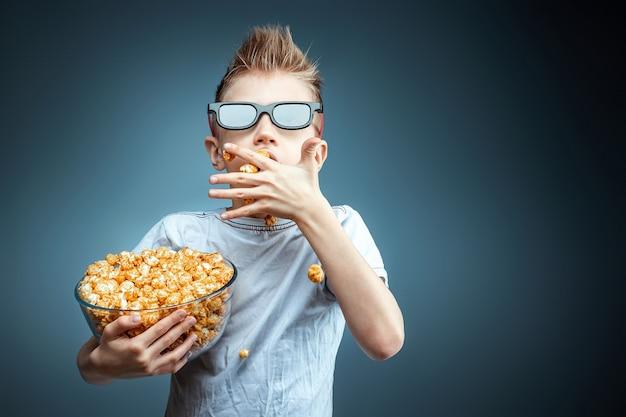 O garoto tem nas mãos e come pipoca assistindo a um filme em 3d óculos, parede azul. o conceito de cinema, filmes, emoções, surpresa, lazer. plataformas de streaming.