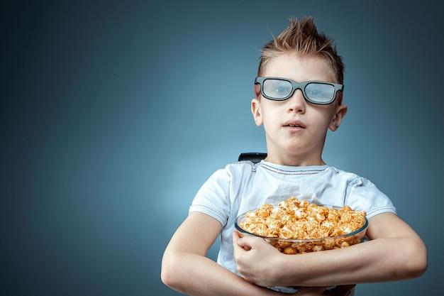 O garoto tem pipoca nas mãos assistindo a um filme em óculos 3d em uma parede azul. o conceito de cinema, filmes, emoções, surpresa, lazer.