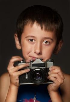 O garoto tira uma foto em uma câmera de filme de 35 mm