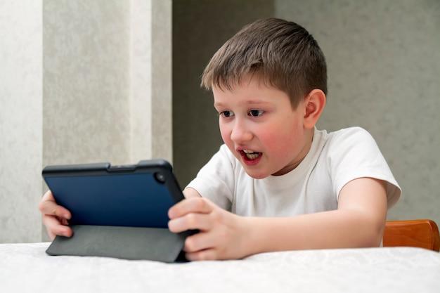 O garoto toca emocionalmente no tablet digital.
