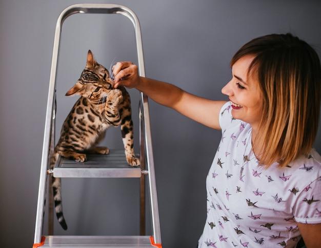 O gato de bengala engraçado joga na escada de aço com uma mulher