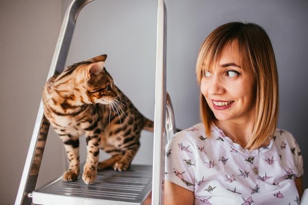 O gato de bengala está na escada atrás de uma mulher bonita