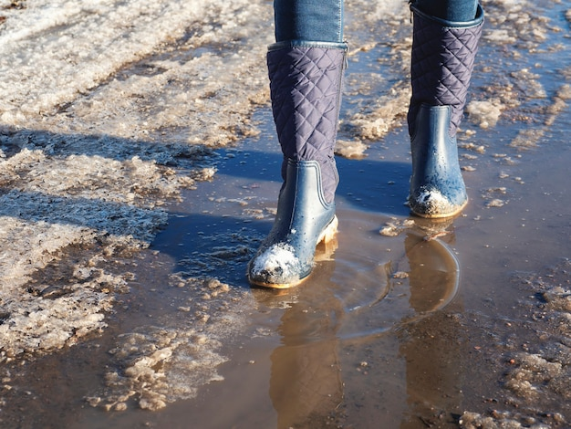 O gelo derrete na primavera, uma mulher atravessa poças d'água na rua, clima de primavera.