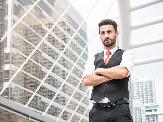 O gerente árabe seguro do homem de negócios que está com braços cruzou exterior no escritório moderno dianteiro.