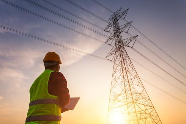 O gerente asiático de engenharia no trabalho de uniforme de segurança padrão inspeciona o polo de alta tensão da eletricidade.