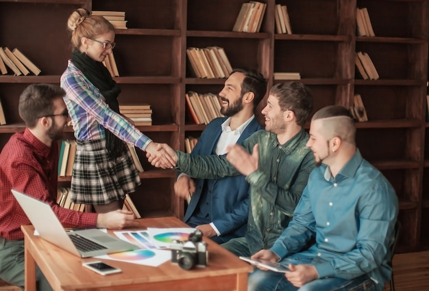 O gerente com um aperto de mão cumprimenta o cliente em um escritório moderno