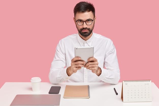 O gerente corporativo usa touchpad para contabilidade, usa óculos ópticos e camisa branca, verifica o relatório, analisa o orçamento