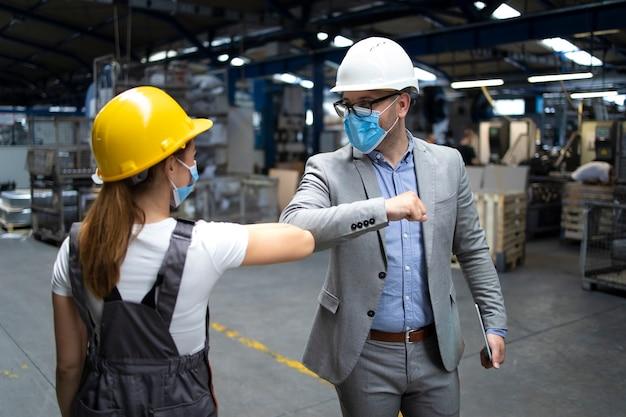 O gerente da fábrica e o trabalhador se cumprimentam com cotoveladas devido à pandemia do vírus corona global e perigo de infecção