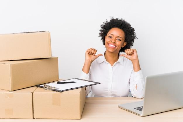 O gerente de armazém sentado, verificando as entregas com um laptop, sente-se orgulhoso e autoconfiante, exemplo a seguir.