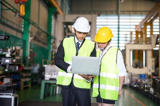 O gerente de auditoria de fábrica asiática sério e o trabalhador com capacete de segurança usam o laptop e o aplicativo corporativo para discutir o resultado da inspeção.