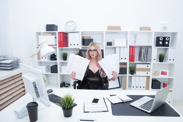 O gerente de escritório analisa um monte de papéis no local de trabalho