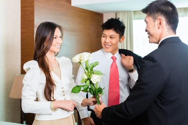 O gerente de hotel ou diretor ou supervisor chinês asiático dá as boas-vindas aos hóspedes vip que chegam com rosas na chegada em um hotel de luxo ou grande