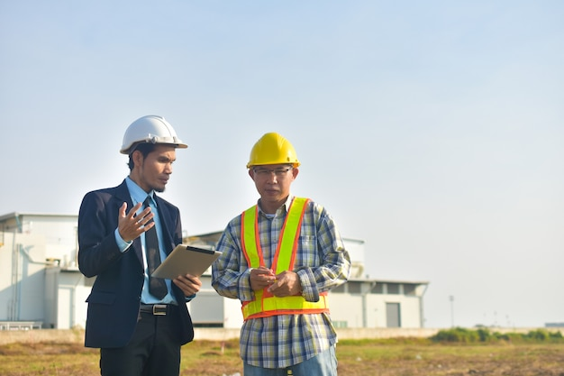 O gerente de projeto e a comunicação do engenheiro usam a fábrica de tablets