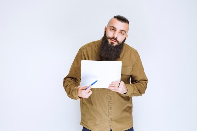 O gerente de projeto mostrando os relatórios a seu colega e marcando os erros ou correções.