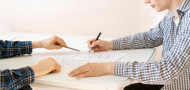 O gerente de rh contrata o novo funcionário para o novo cargo, senta-se à mesa e entrevista