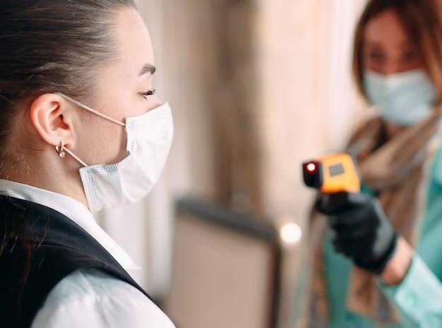 O gerente de um restaurante ou hotel verifica a temperatura corporal dos funcionários com um aparelho de imagem térmica.