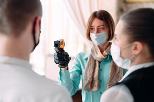 O gerente de um restaurante ou hotel verifica a temperatura corporal dos funcionários com um dispositivo de imagem térmica.