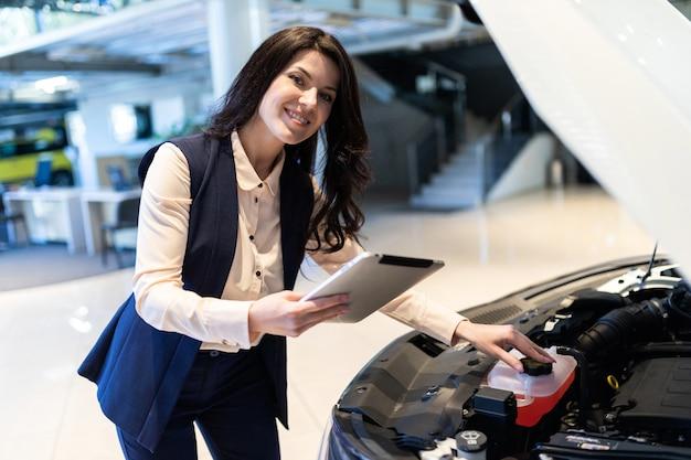 O gerente de venda bonito inspeciona o carro novo com a ajuda do tablet no centro da concessionária