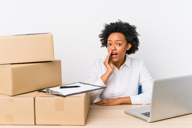 O gerente do armazém sentado, verificando as entregas com o laptop, está dizendo uma notícia secreta sobre a travagem e olhando para o lado