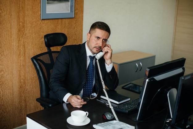 O gerente está ao telefone em seu escritório