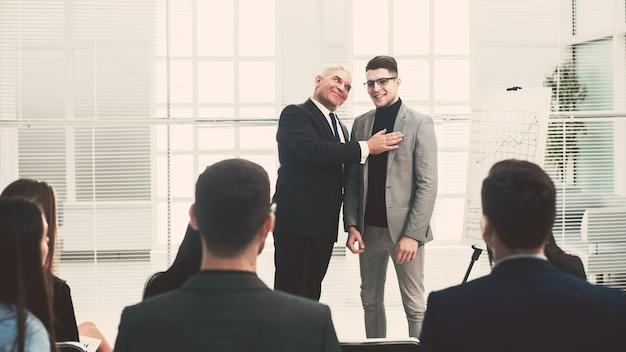 O gerente está apresentando um novo funcionário da empresa em uma reunião com a equipe de negócios.
