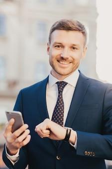O gerente executivo masculino alegre bonito bem vestido verifica o tempo em seu relógio de pulso