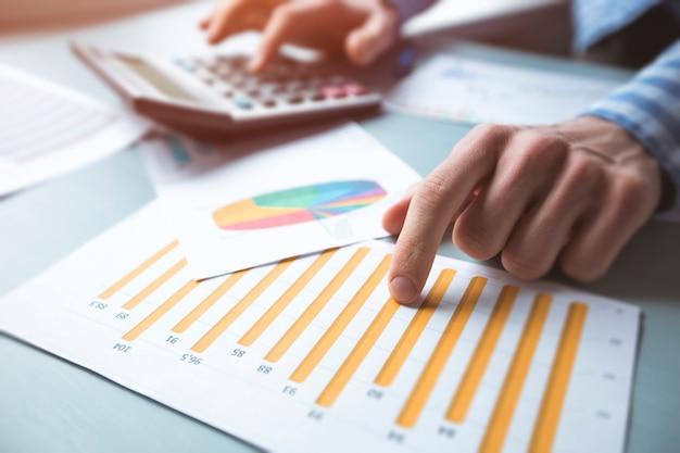 O gerente faz um relatório financeiro contando com a calculadora e referindo-se aos dados estatísticos no gráfico.