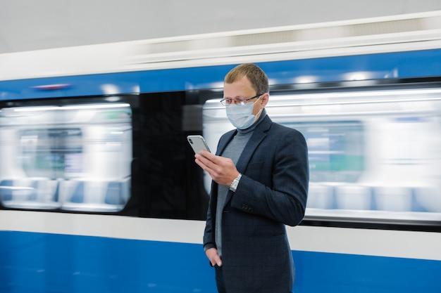 O gerente jovem usa celular, evita a disseminação do coronavírus, posa contra o trem do metrô, posa na plataforma, verifica notícias on-line, usa máscara médica. situação epidêmica, conceito de cuidados de saúde
