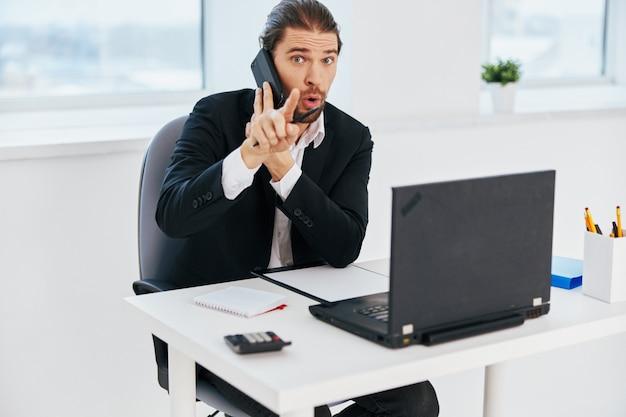 O gerente na mesa documenta a comunicação do chefe do telefone