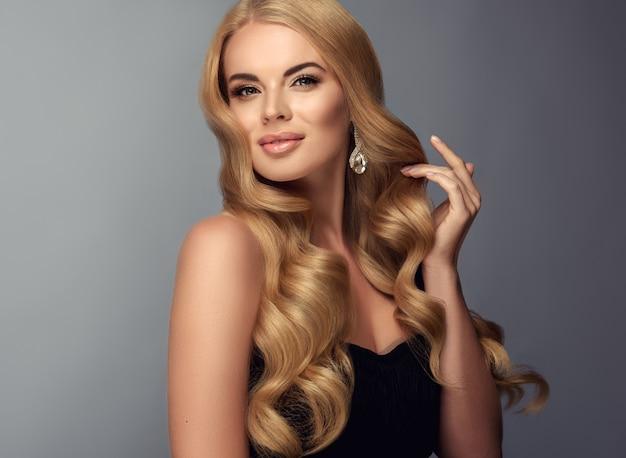 O gesto suave de dedos delgados abre excelentes cachos de cabelo loiro e mostra o brinco feito de pedras brilhantes. sorriso terno na mulher de cabelos loiros. cabelo ondulado. beleza e elegância.