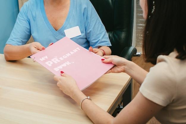 O ginecologista entrega à menina um diário de gravidez. meu livro grávido.